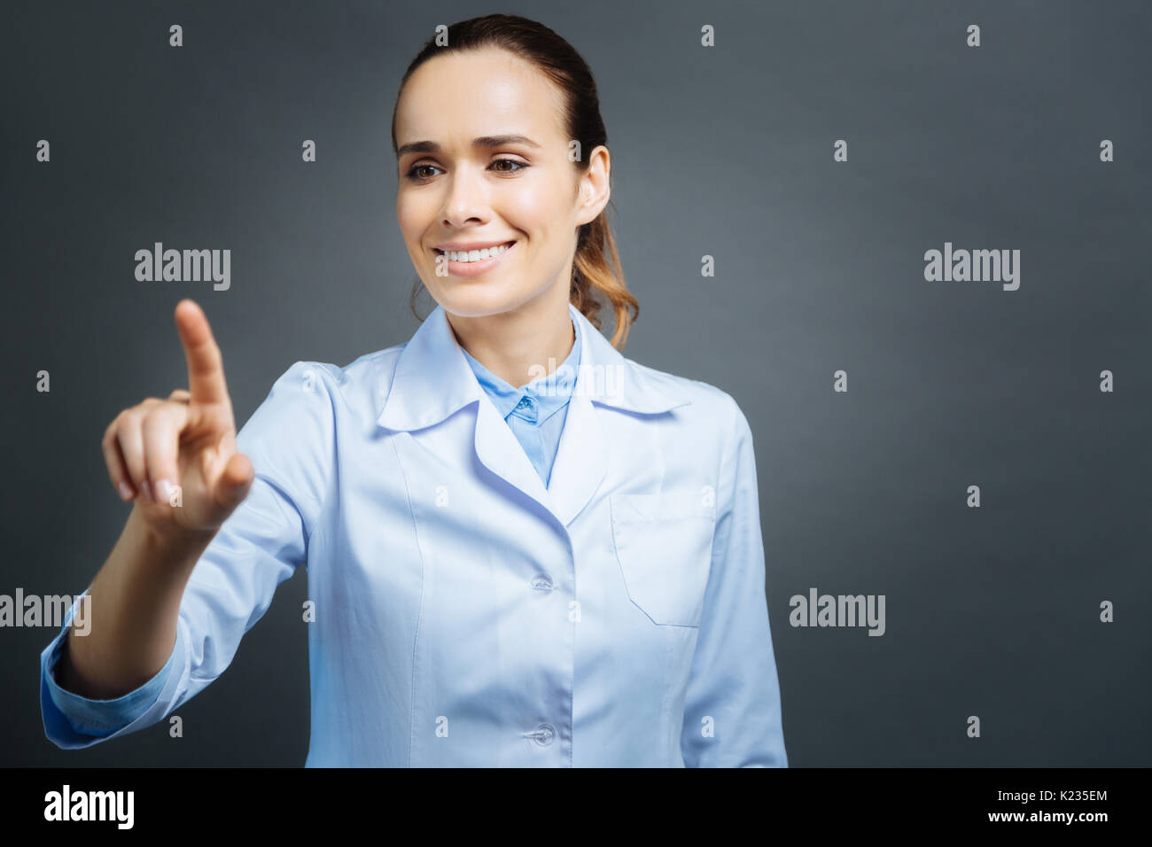 Beautiful medical professional using invisible touchscreen - Stock Image