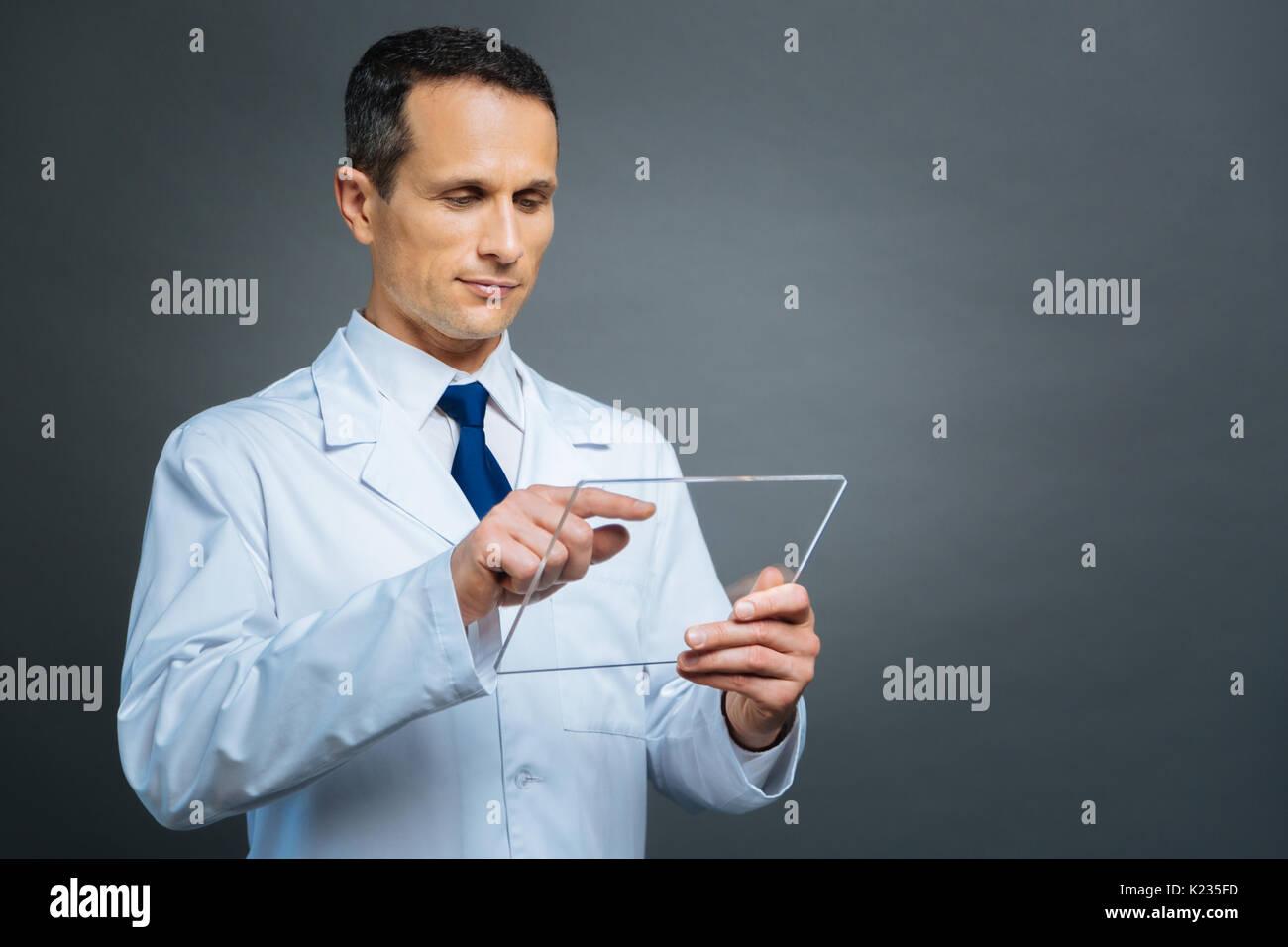 Serious medical working on transparent gadget - Stock Image