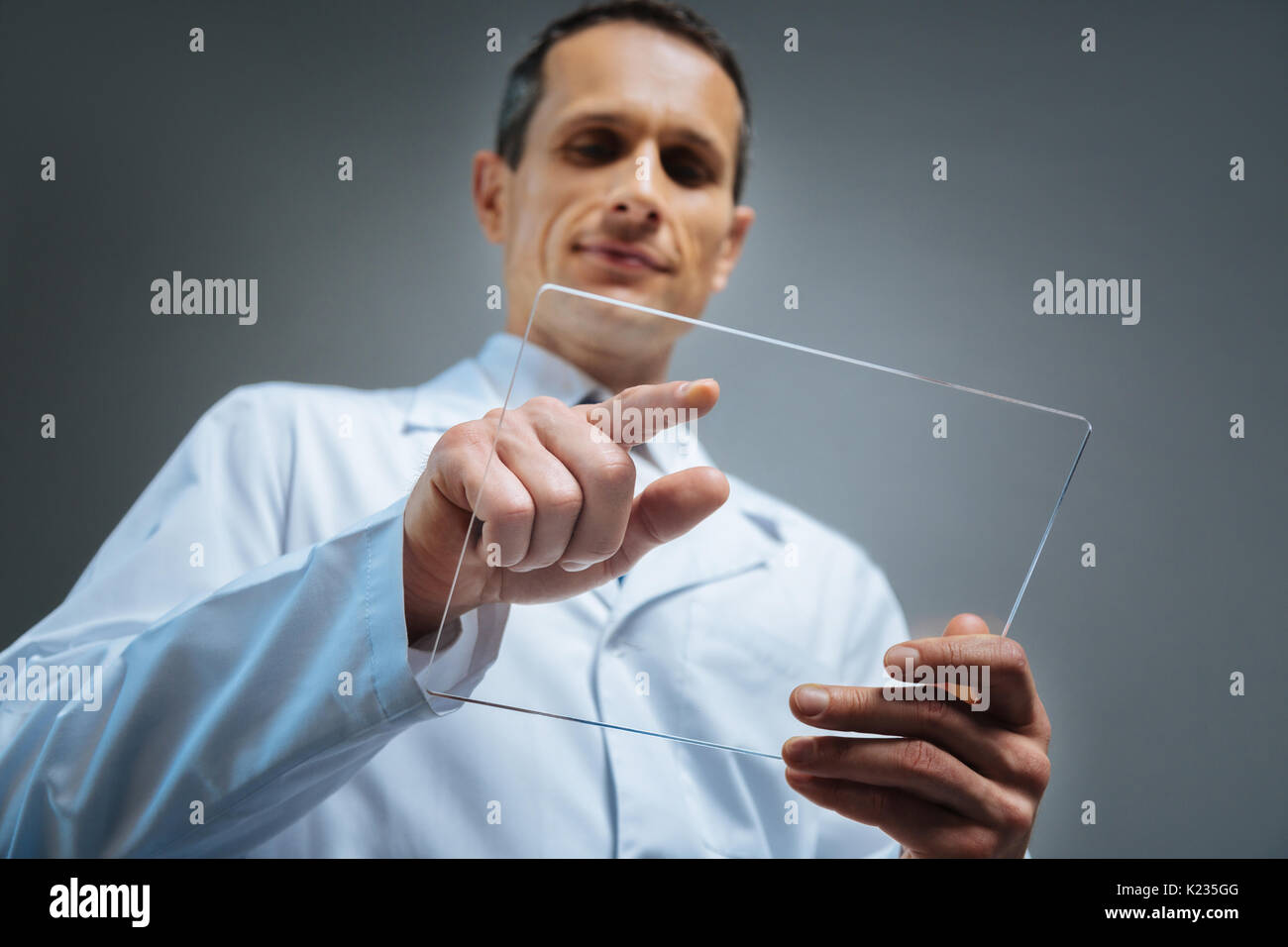 Selective focus on transparent gadget held by mature man Stock Photo