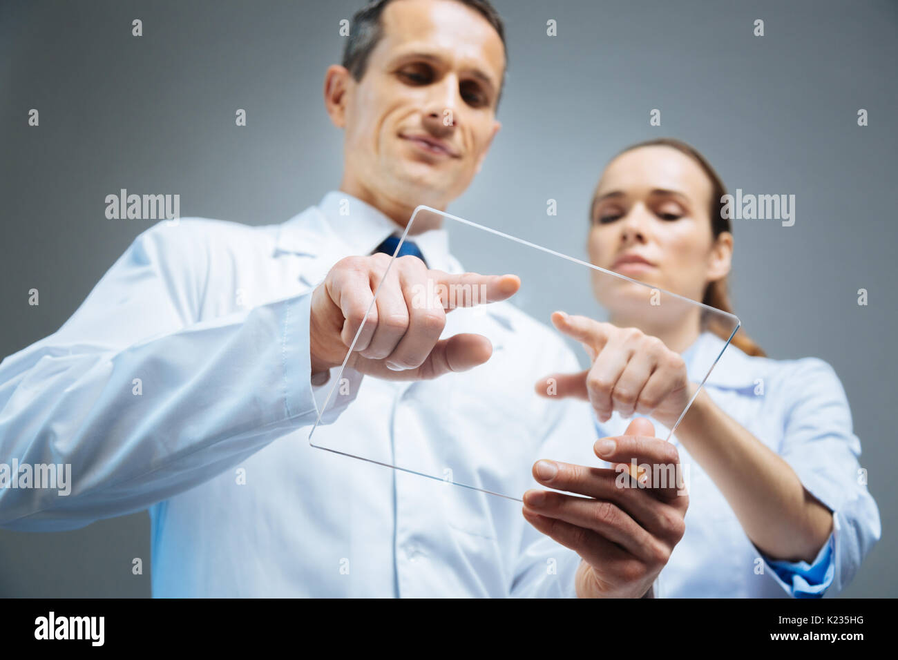 Colleagues working on transparent tablet together - Stock Image
