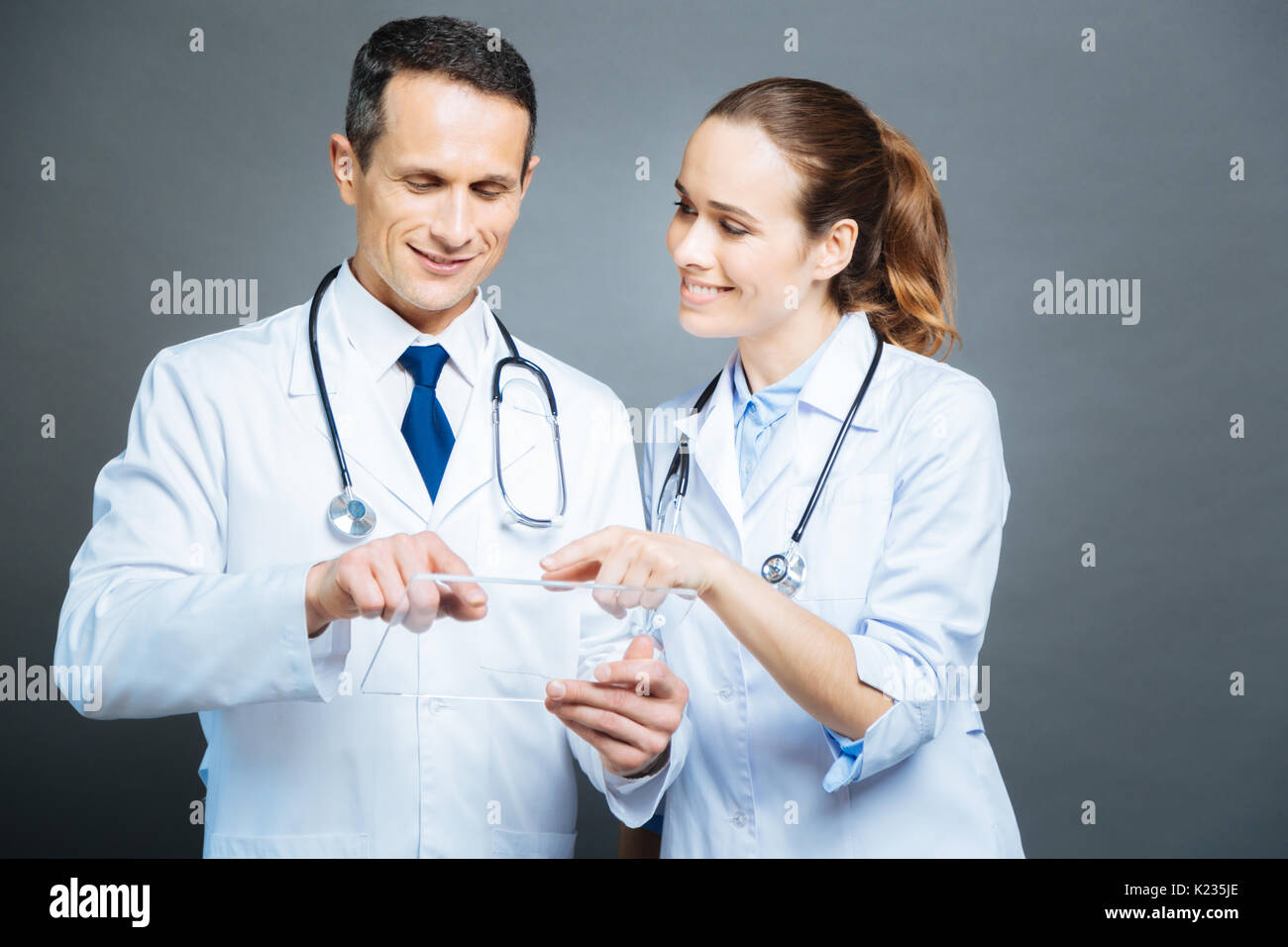 Friendly doctors touching screen of transparent tablet - Stock Image