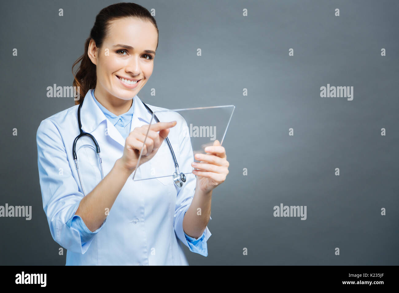 Beaming young lady in white coat posing with transparent tablet - Stock Image