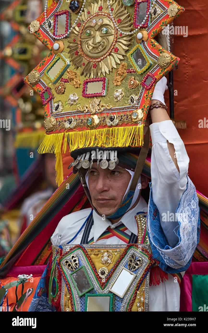 June 17, 2017 Pujili, Ecuador: large religious headdress balanced on male dancers head during Corpus Christi parade - Stock Image