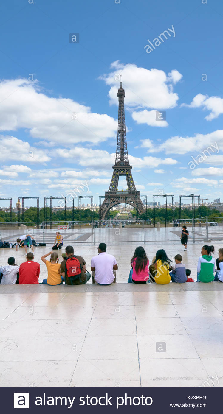 People sitting and relaxing on the trocadero looking at the Eiffel tower in France Europe - Stock Image