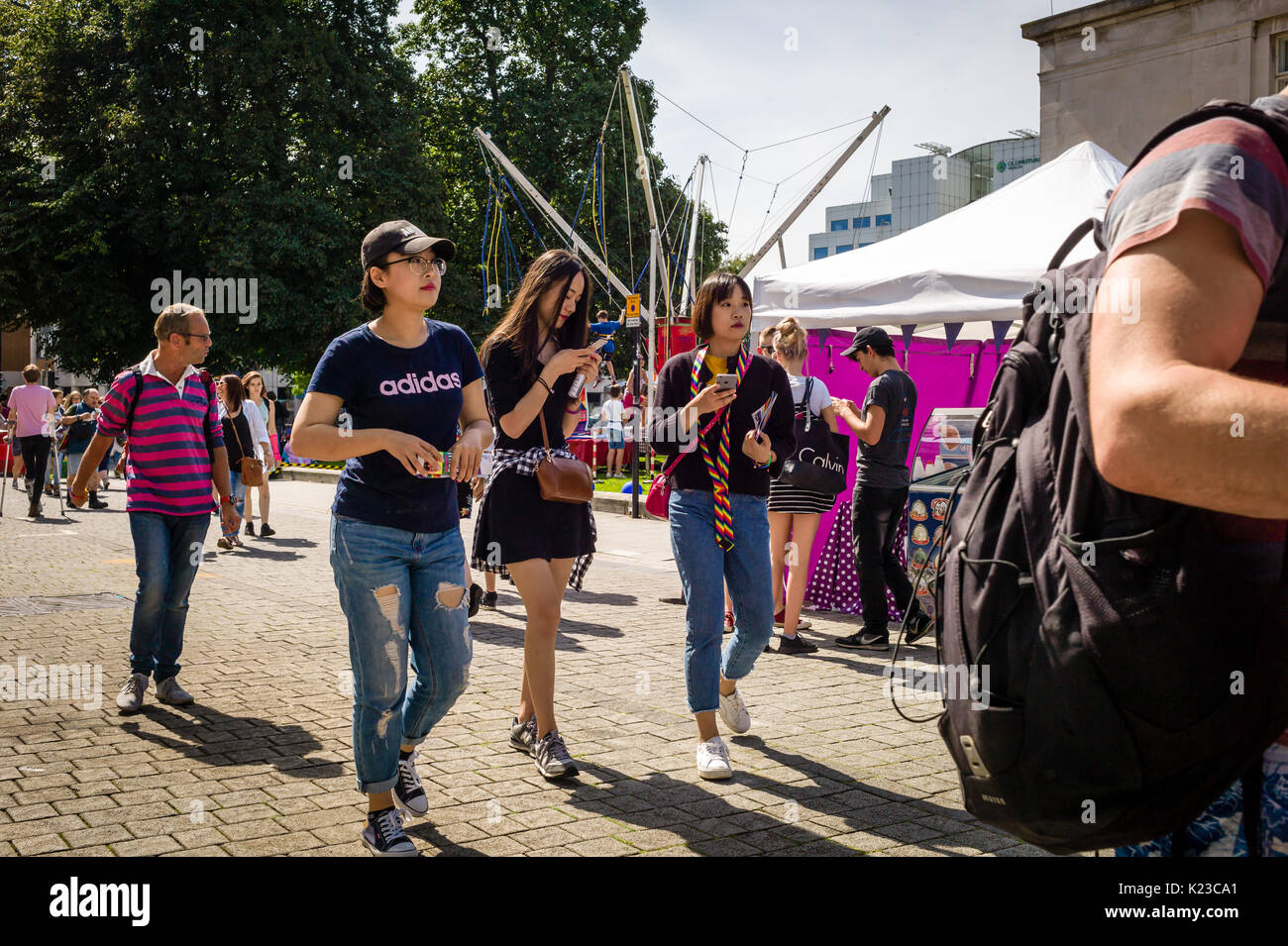 Three oriental girls walk through a Gay Pride event. Two of them are holding mobile phones. One is wearing torn jeans. All three are casually dressed. - Stock Image