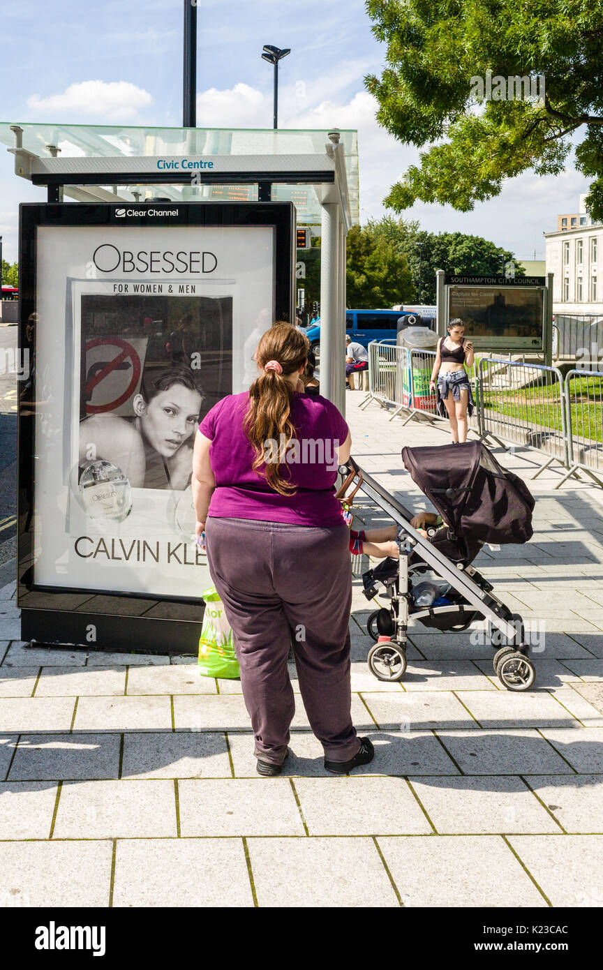A large woman stands in front of a bus stop featuring an advertisement for a perfume brand illustrated with an attractive model. Is the woman envious - Stock Image