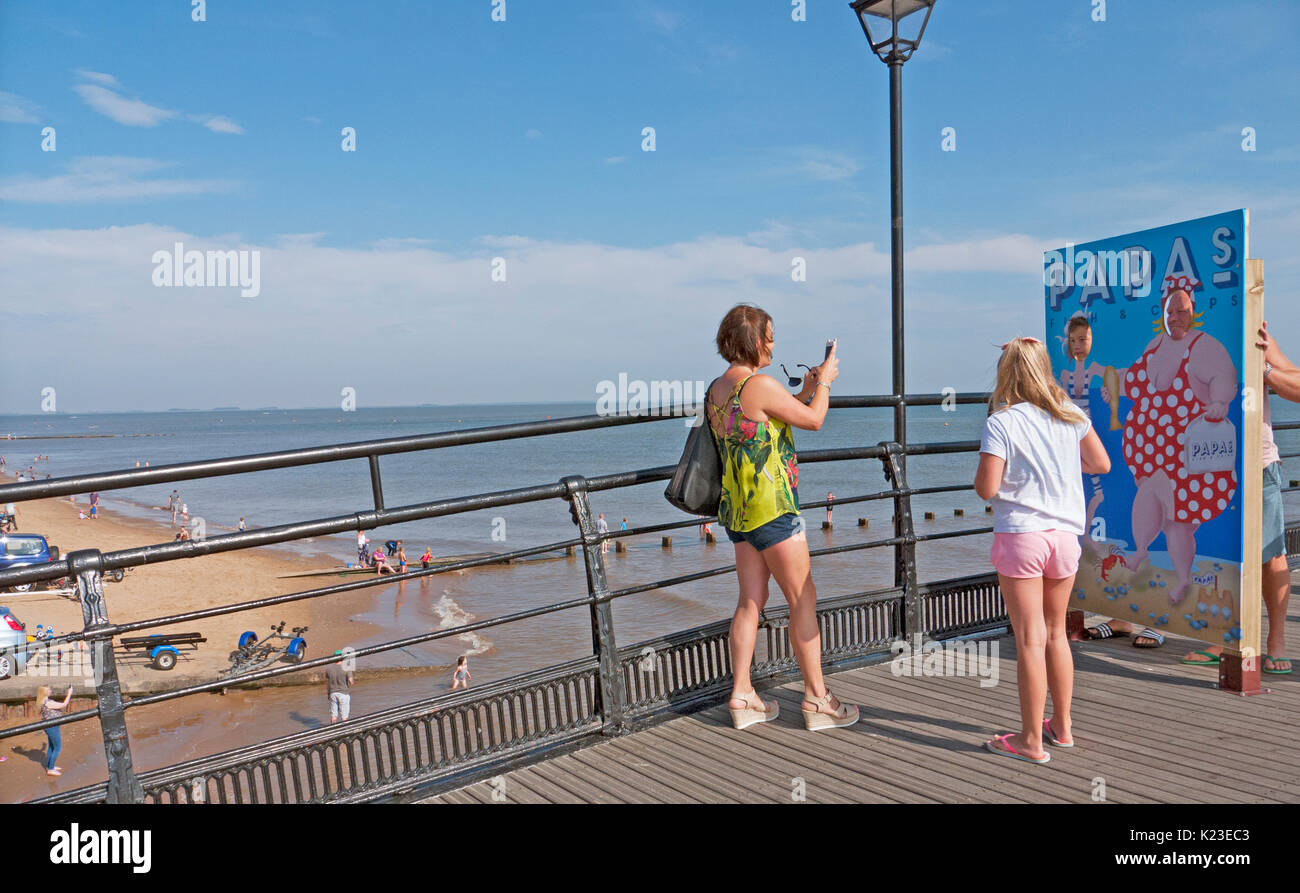 Kids photograph parents faces through face poster hoarding on Cleethorpes pier. - Stock Image