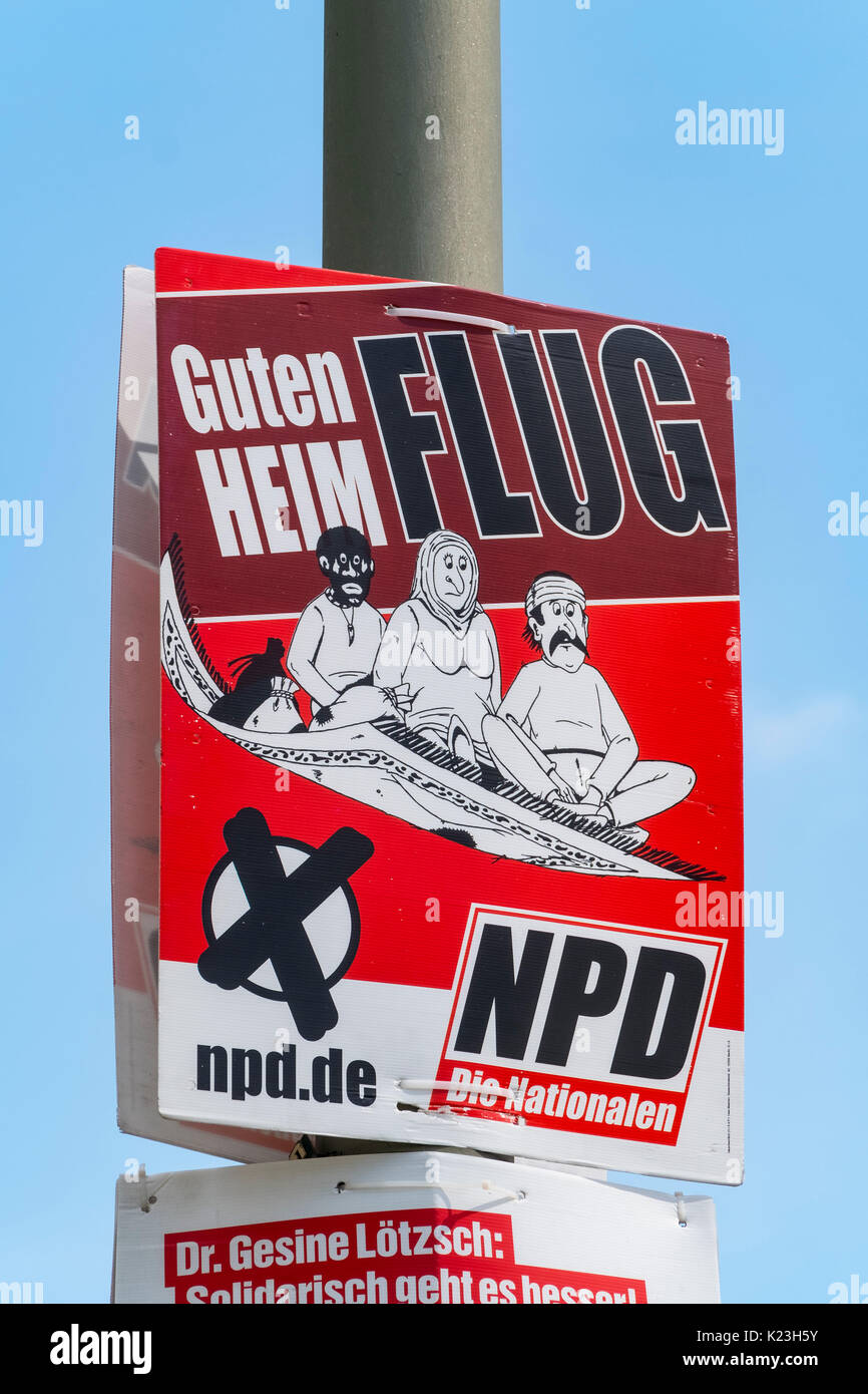 Berlin, Germany. 28th August 2017. Party political poster for far-right neo-Nazi NPD party, National Democratic Party of Germany with message 'Have a good Flight Home' featuring migrants on flying carpet, in Eastern district of Berlin for Federal elections on 24th September 2017. Credit: Iain Masterton/Alamy Live News - Stock Image