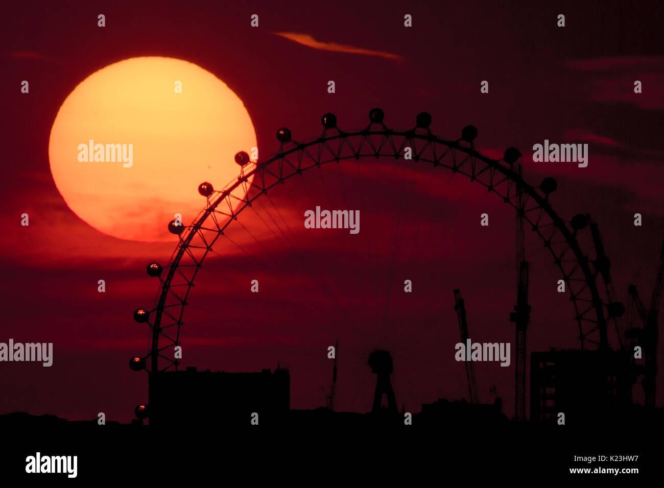 London, UK. 28th August, 2017. UK Weather: Dramatic sunset behind London Eye Ferris Wheel ending the bank holiday heatwave © Guy Corbishley/Alamy Live News - Stock Image