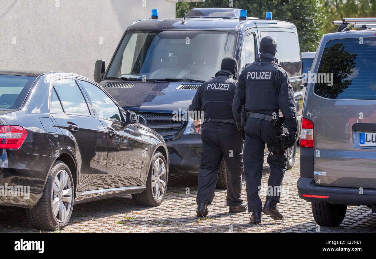 Banzkow, Germany. 28th Aug, 2017. Police officers of a special unit walk on a property in Banzkow, Germany, 28 August 2017. Officers of the Federal Office for Criminal Investigation and the federal police searched apartments and offices in several places in Mecklenburg-Western Pomerania. The preparation of a subversive act of violence is suspected. Photo: Jens Büttner/dpa-Zentralbild/dpa/Alamy Live News - Stock Image