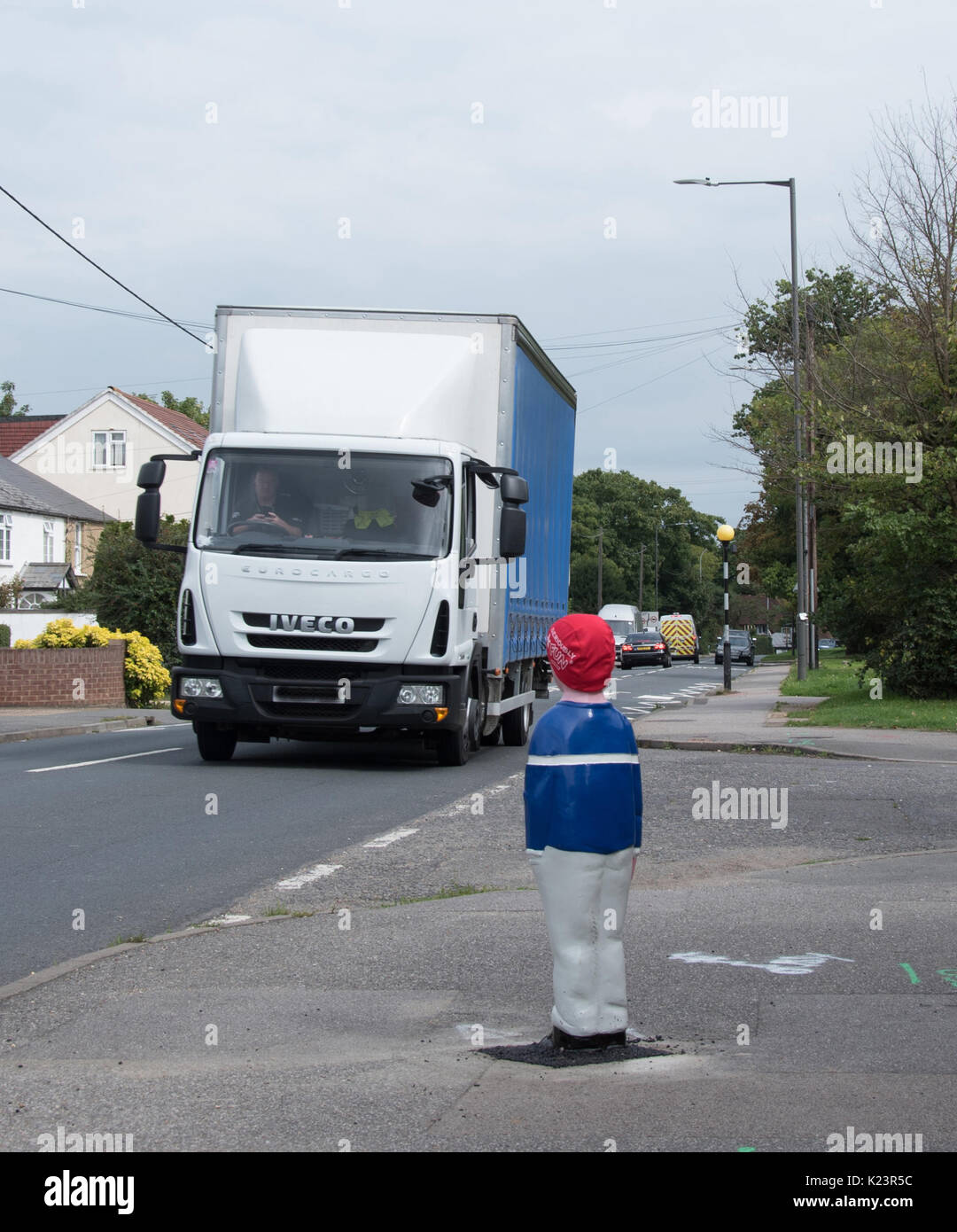 106a939ca1 texting at wheel of HGV outside Infants School - Stock Image