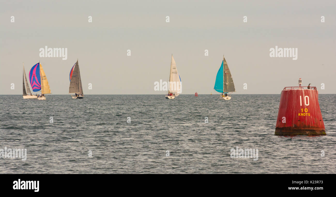 Poole, Dorset, UK, 29th August 2017. UK Weather. Sailing in the evening sunshine. The sailors pilot their vessels to pick up light winds which propel them out from the harbour and into Poole Bay and the open sea. Credit: Paul Biggins/Alamy Live News - Stock Image