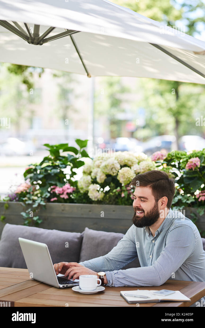 Smiling Bearded Businessman Working in outdoor Cafe - Stock Image