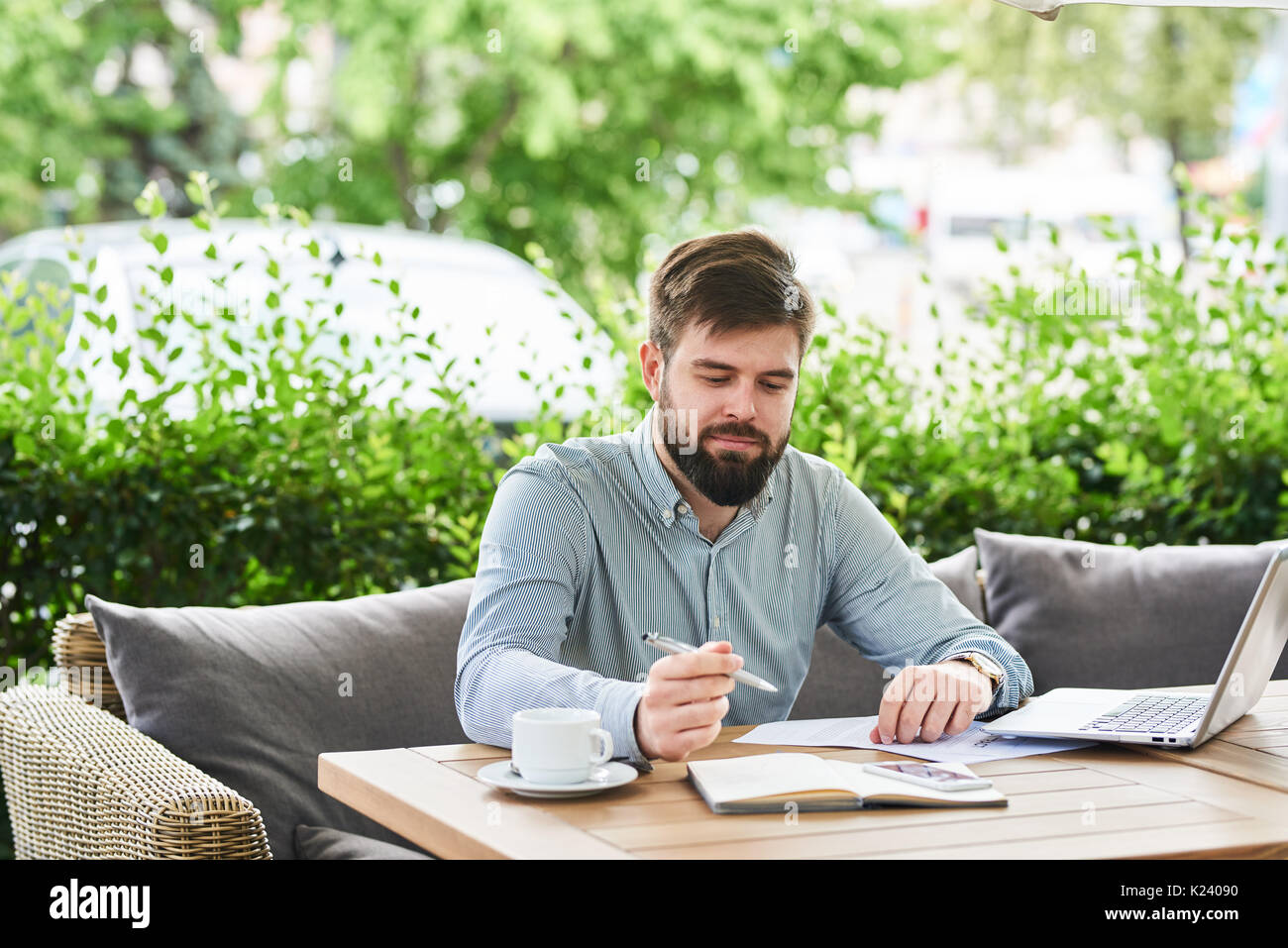 Smiling Businessman Enjoying Working in Cafe - Stock Image