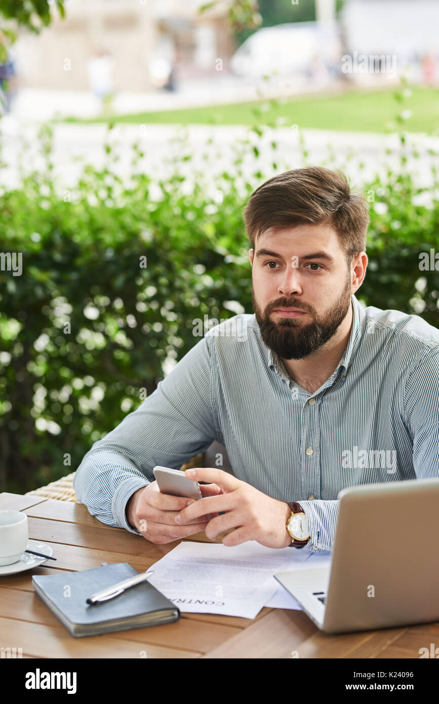 Pensive Businessman  Working in Cafe Outdoors - Stock Image