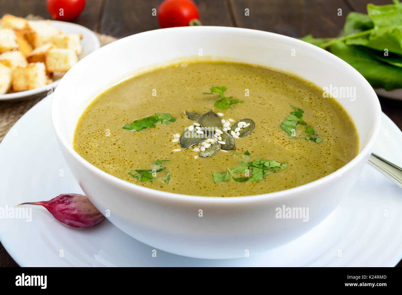 Vegetable cream soup with spinach and potatoes in a white bowl with garlic croutons on a dark wooden background. Dietary vegetarian menu. Proper nutri - Stock Image