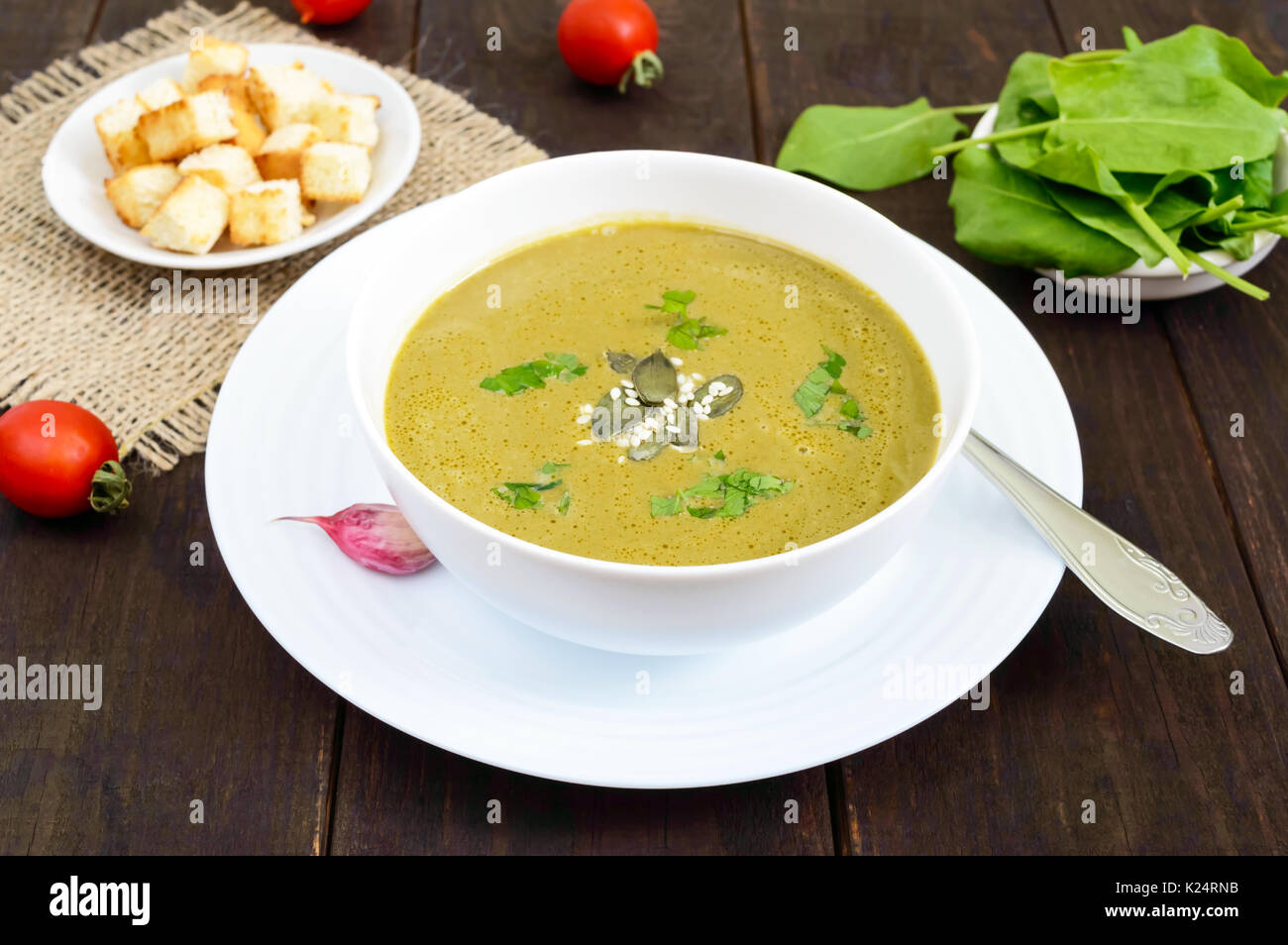 Vegetable cream soup with spinach and potatoes in a white bowl with garlic croutons on a dark wooden background. Stock Photo