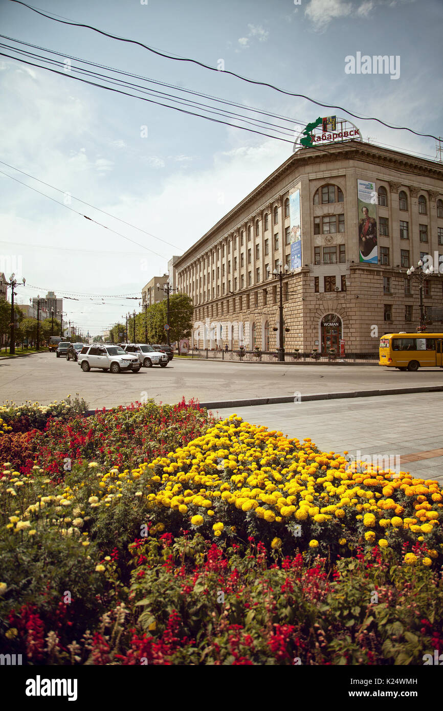 City of Khabarovsk downtown cityscape with flowers. Classical old architecture on a central town street in summer. RANEPA university at Lenin square - Stock Image