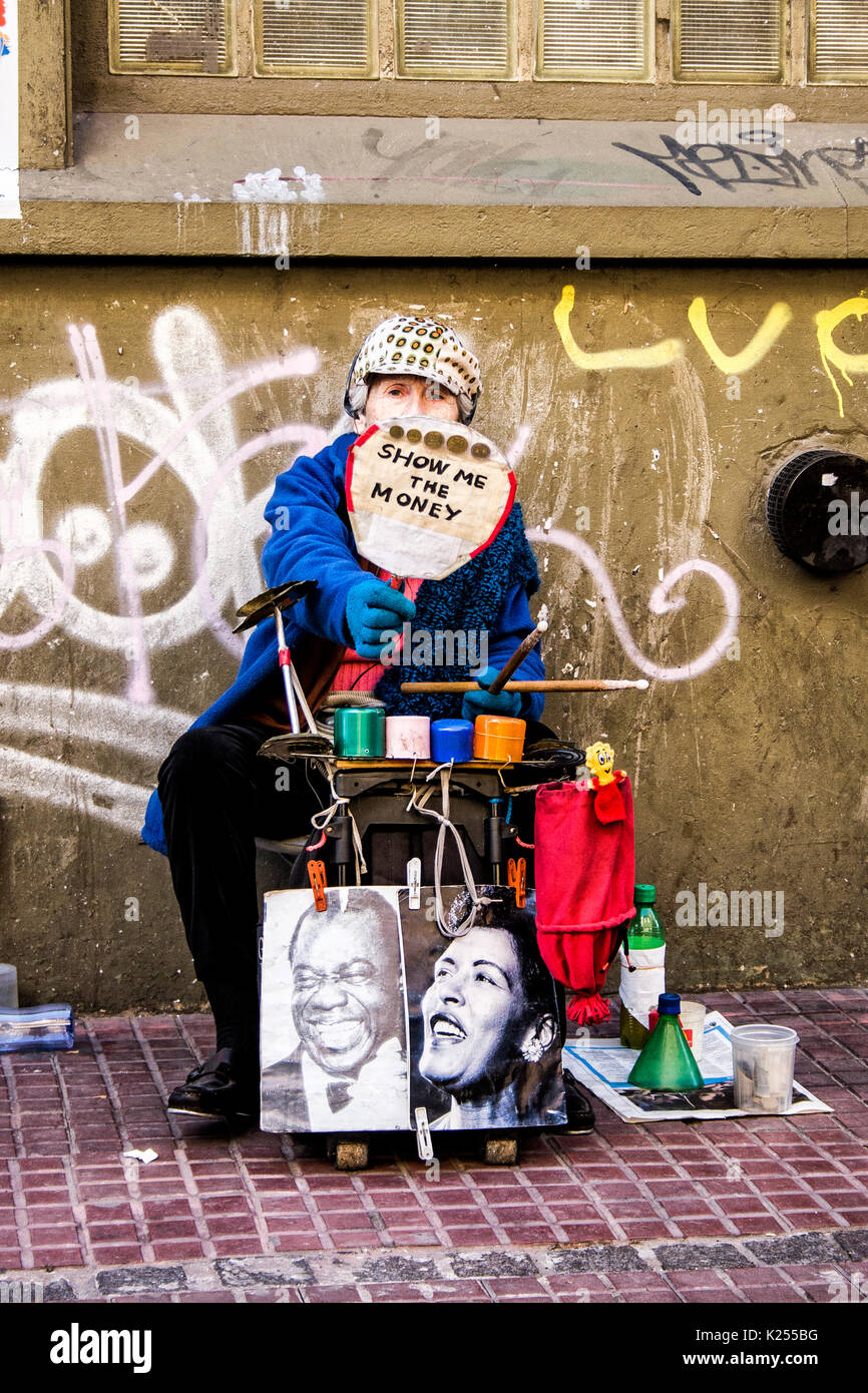 Elder woman showing a poster on the street in San Telmo neighborhood. Buenos Aires, Argentina. - Stock Image