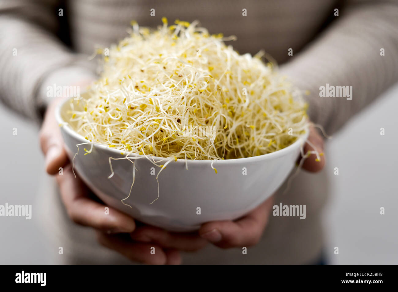 closeup of a young caucasian man with a white ceramic bowl full of alfalfa sprouts - Stock Image