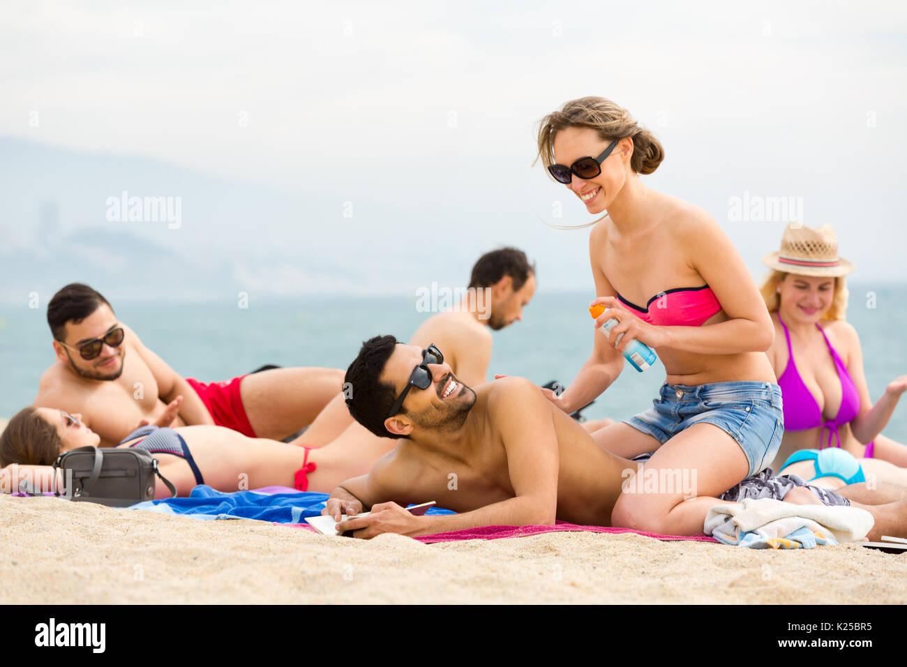 Beach attendant rubs suntan oil on angelys 5