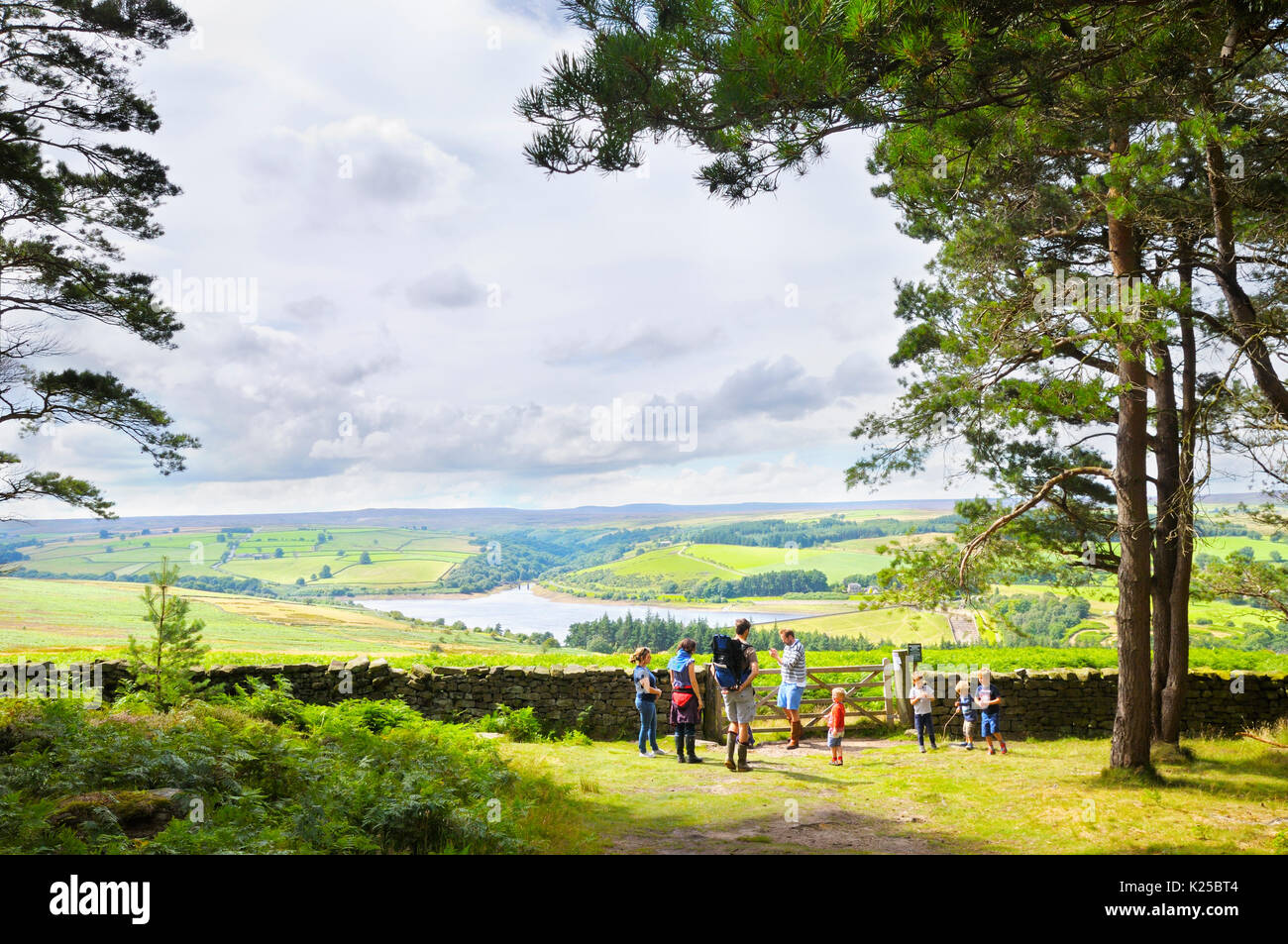 Families on a woodland walk pause for a break to enjoy the views of the Yorkshire countryside around Leighton Reservoir, Ilton, North Yorkshire, UK - Stock Image