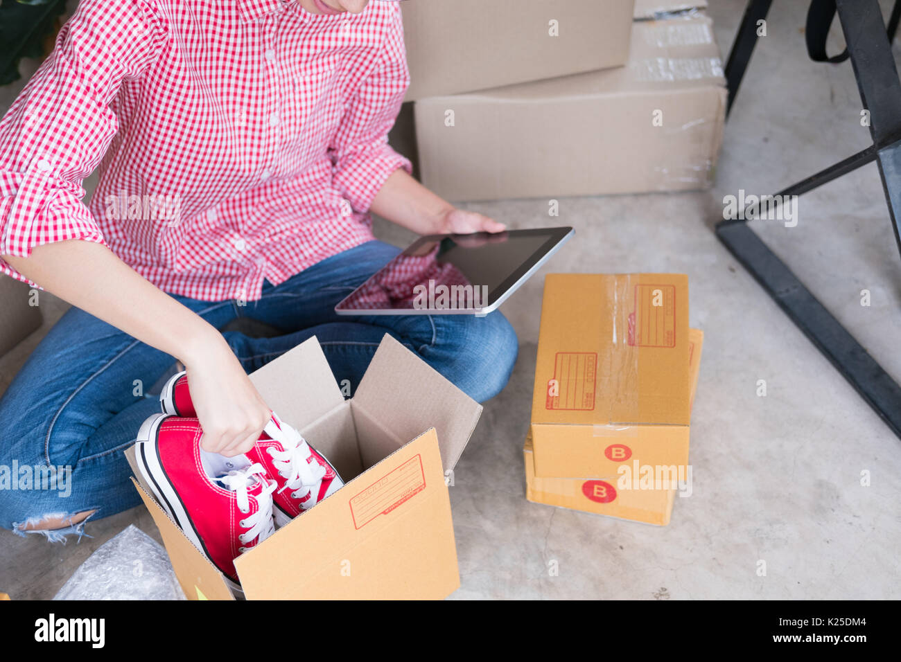 young start up small business owner packing shoes in the box at