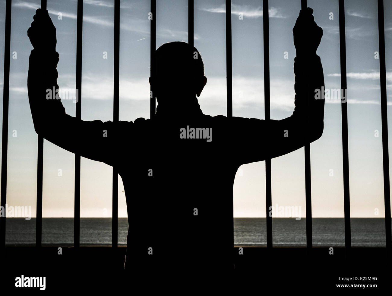 Silhouette of man looking through steel bars with sea in background. Depression, mental health, asylum seeker, immigration... concept image. - Stock Image