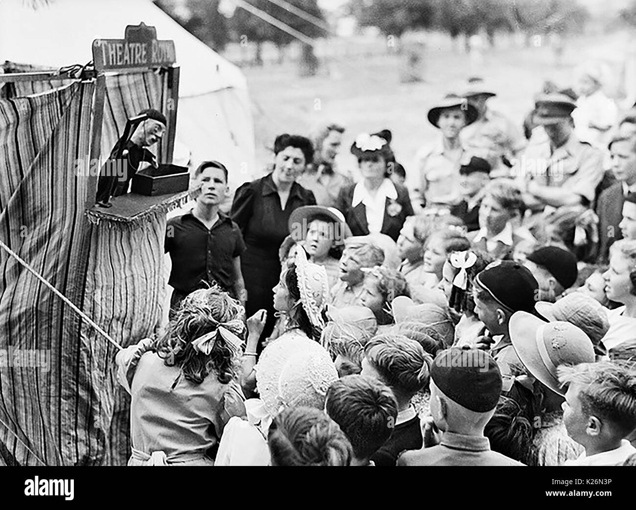 A wartime punch and Judy children's entertainment show - Location unknown but children's sun hats and Australian troops in background suggest Australia - Stock Image