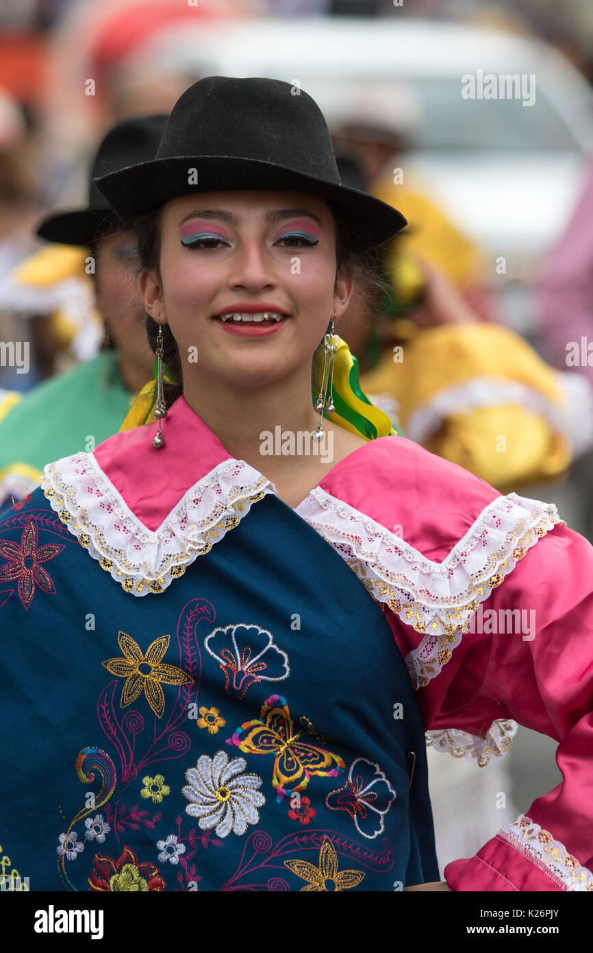 June 17, 2017 Pujili, Ecuador: young indigenous woman in bright color traditional clothing at Corpus Christi parade dancing in the street Stock Photo