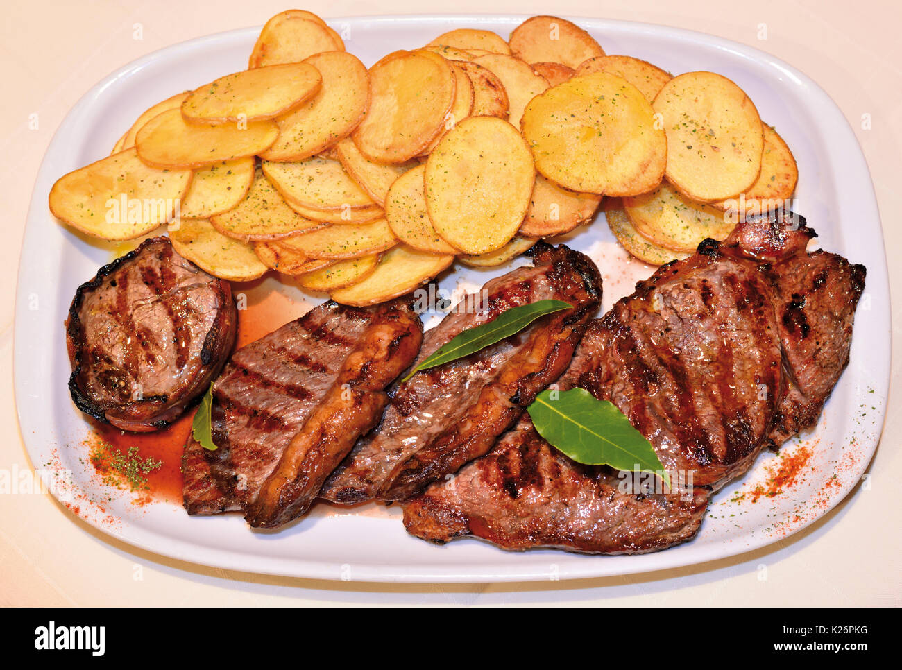 Plate with fried potatoes and grilled meat - Stock Image