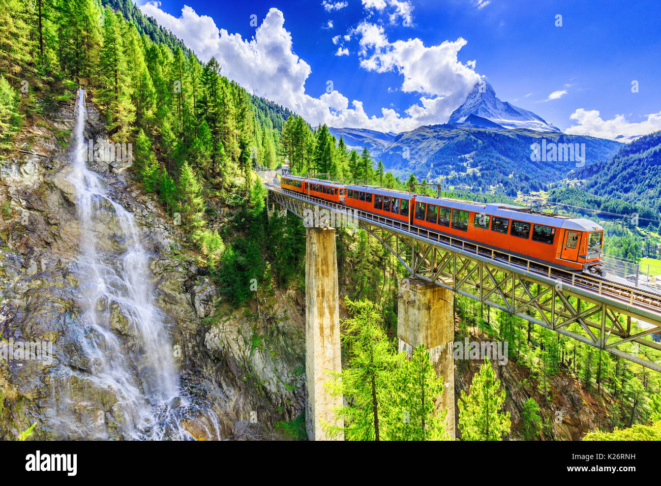 Zermatt, Switzerland. Gornergrat tourist train with waterfall, bridge and Matterhorn. Valais region. - Stock Image