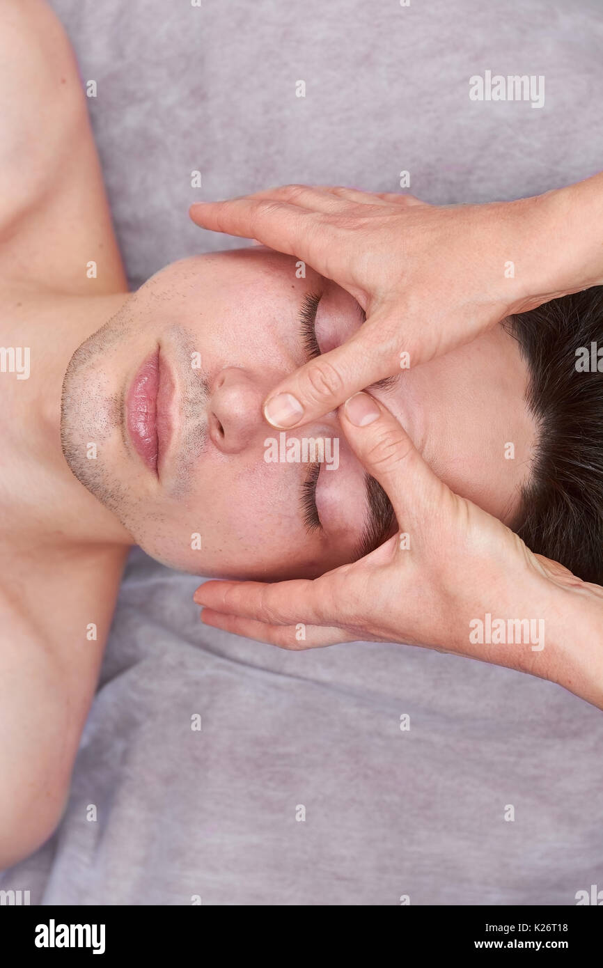 Male face, hands of masseuse. Facial massage, top view. Stock Photo