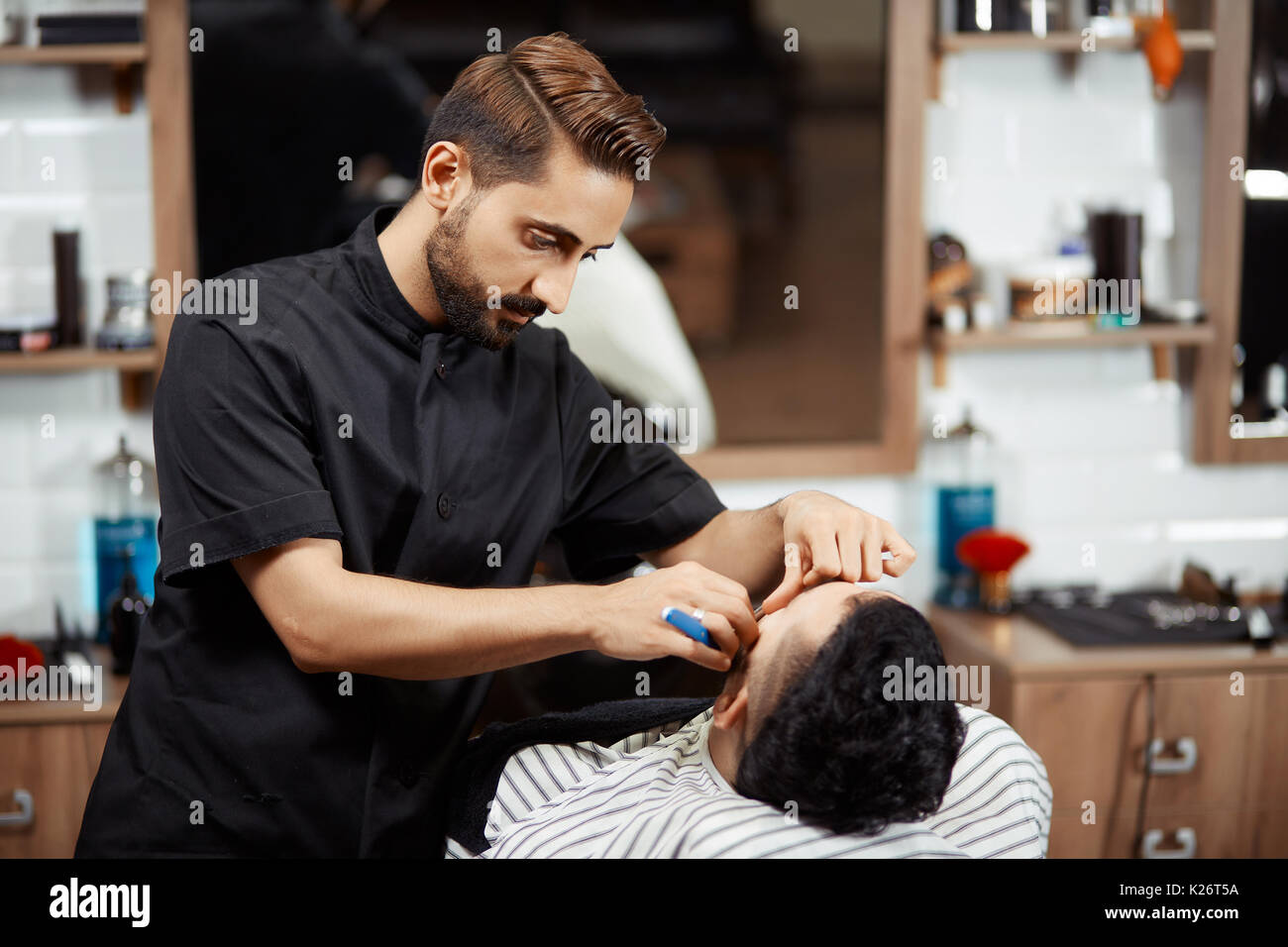 Hairstylist cutting bread of client in modern barber. - Stock Image