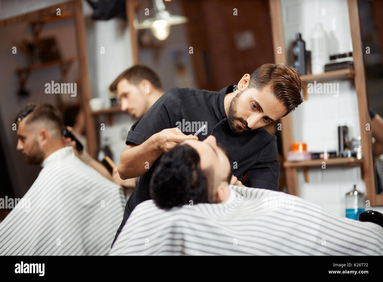 Two stylists cutting bread, making haircut for clients in barber shop. - Stock Image