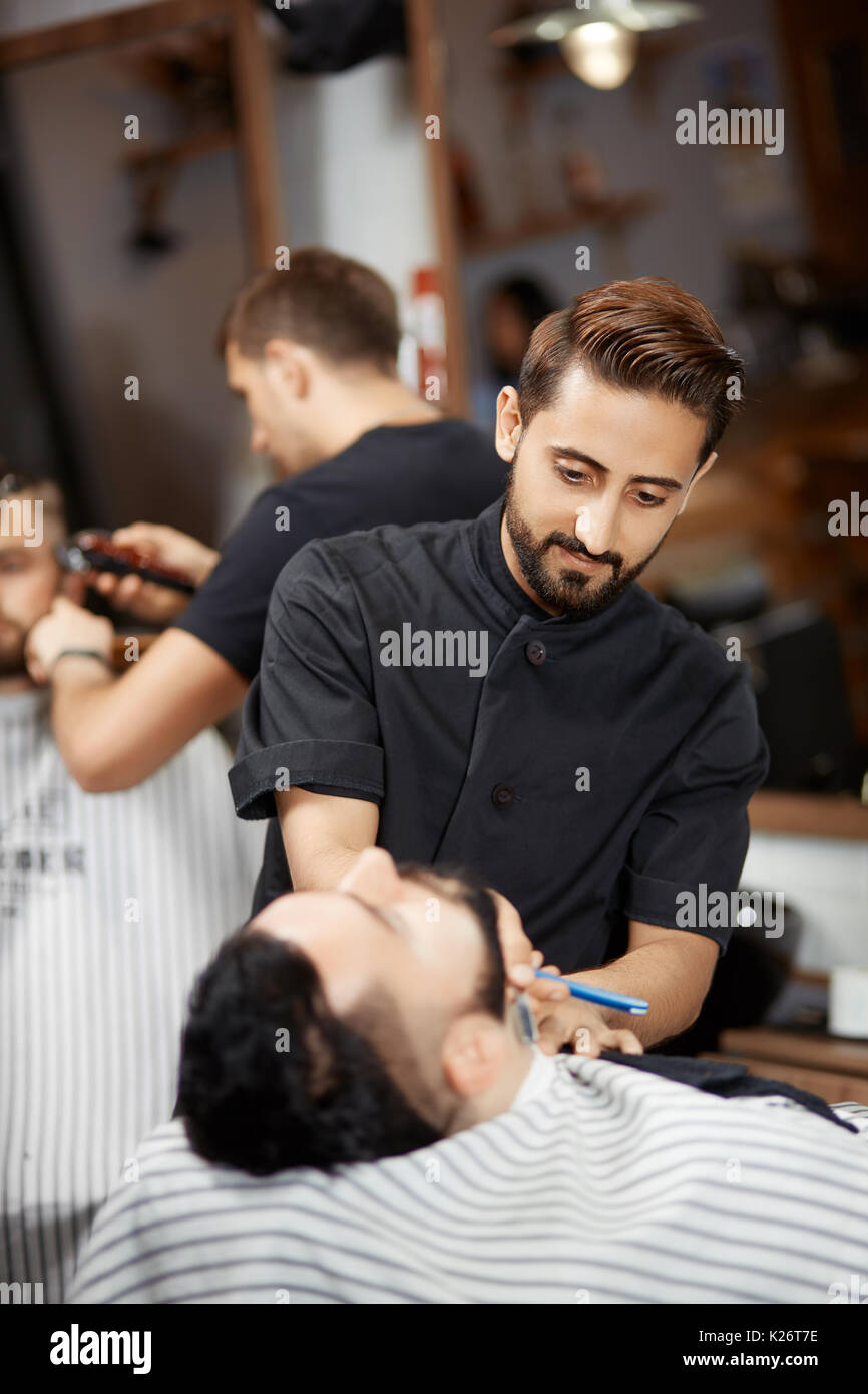 Handsome hairstylist in barber shop cutting bread with razor for brunet man. - Stock Image