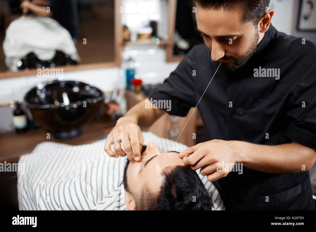Hairdresser in black cutting bread for brunet man with thread. - Stock Image