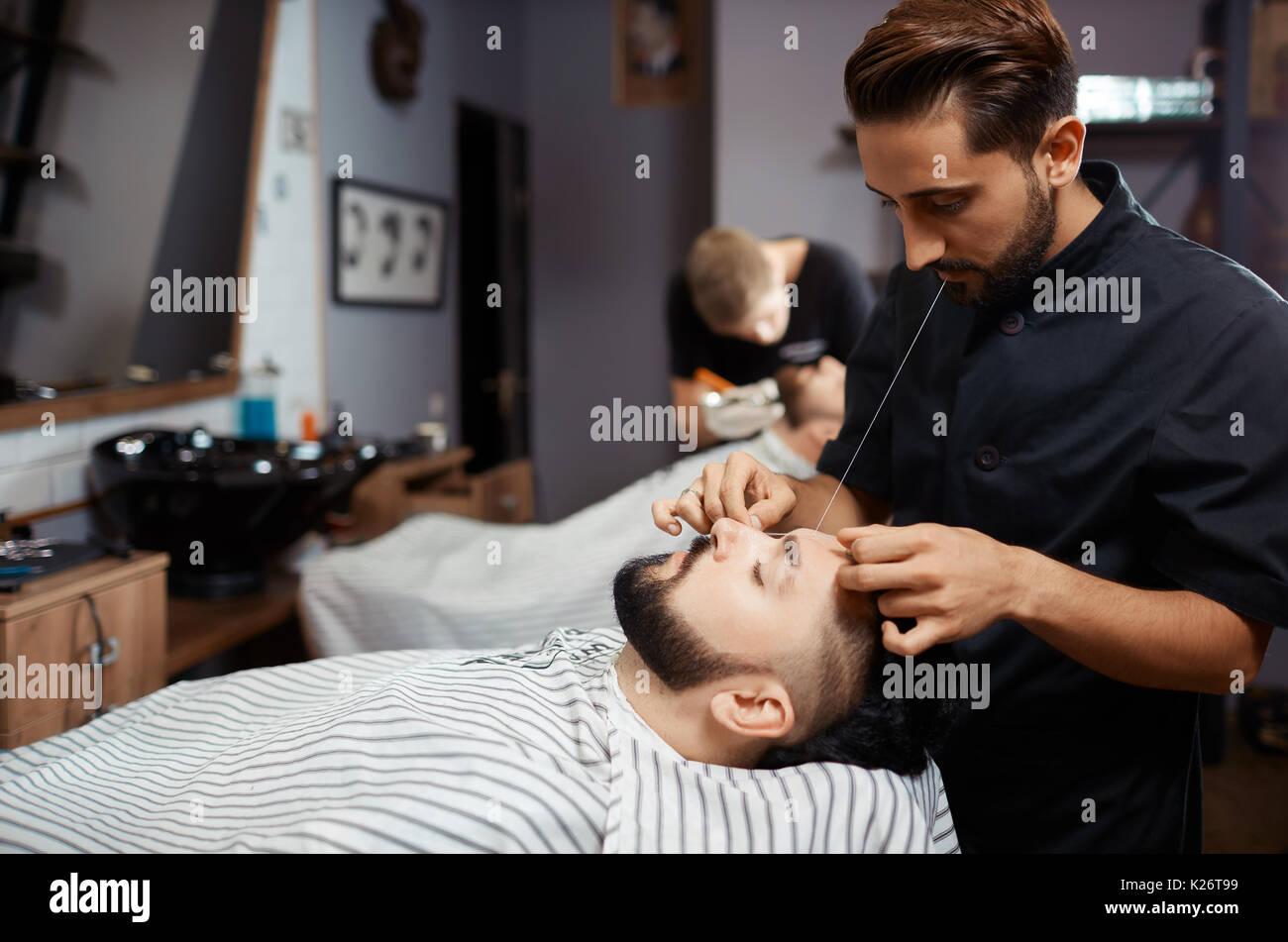 Brunet man visiting barbershop for  cutting beard of thread. - Stock Image