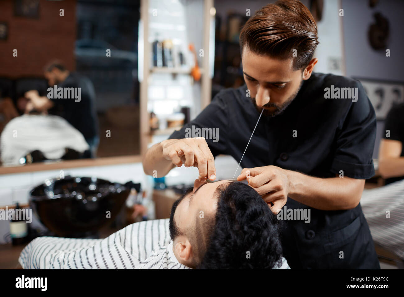 Professional hairdresser doing correction of bread with thread. - Stock Image