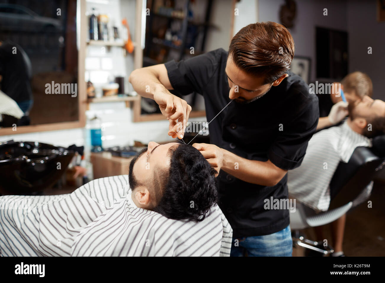 Hairdresser doing correction and cutting bread in modern barbershop. - Stock Image