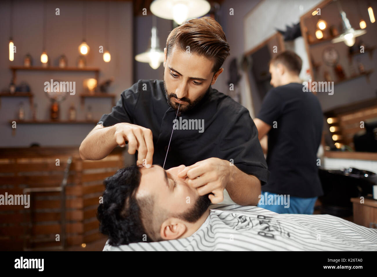 Hairdresser working at barbershop, correcting bread with white thread. - Stock Image