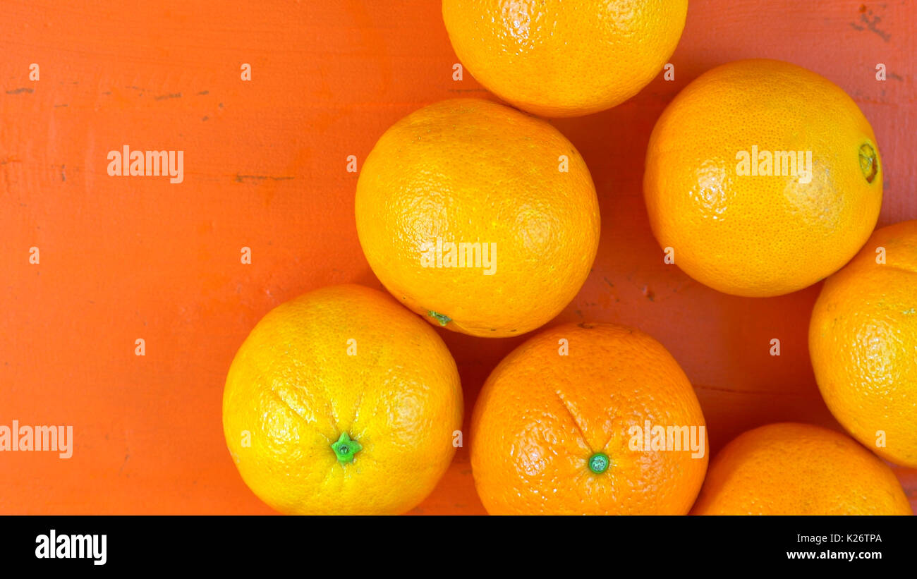 Oranges on ornage wood table overhead, with copy space. - Stock Image