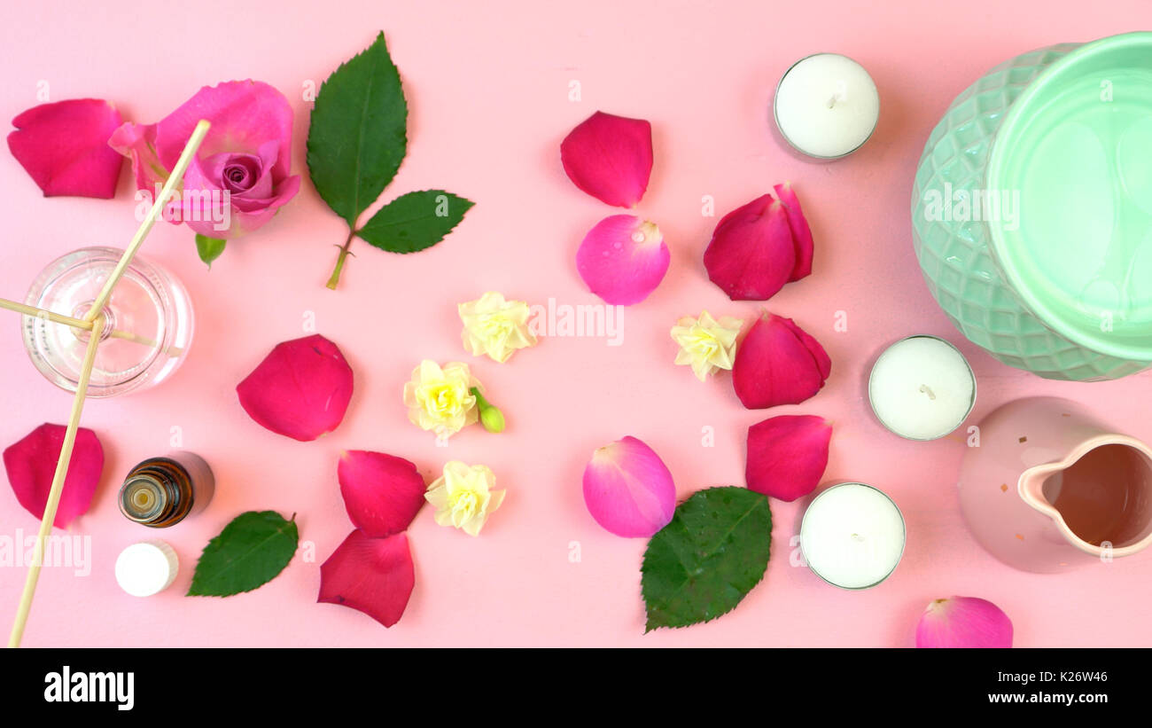 Aromatherapy overhead flatlay display of oil burner, mood sticks, essential oil and scattered rose petals on feminine Stock Photo