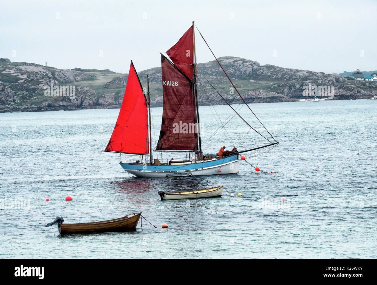Sailing ship with red sails, Iona Island, Inner Hebrides, Scotland, United Kingdom - Stock Image