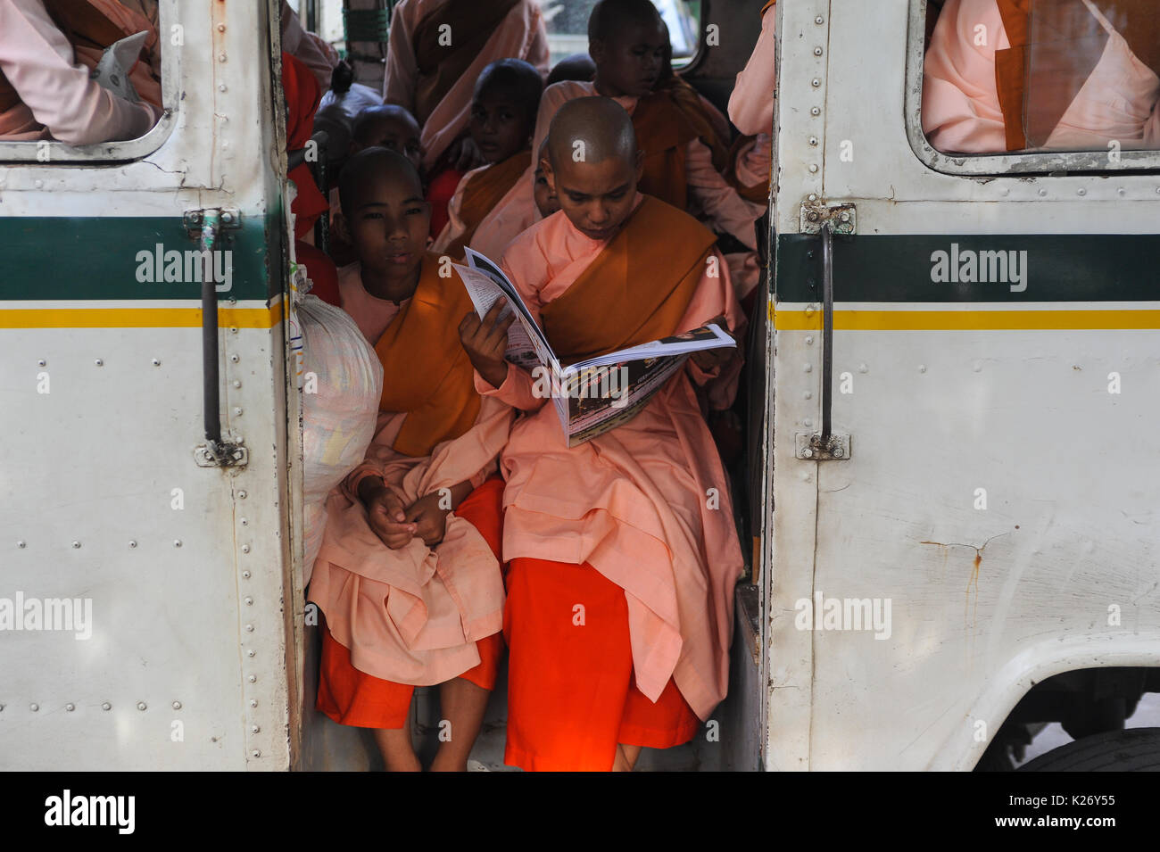10.10.2013, Yangon, Republic of the Union of Myanmar, Asia - A Buddhist nun is reading a newspaper on a waiting bus. - Stock Image