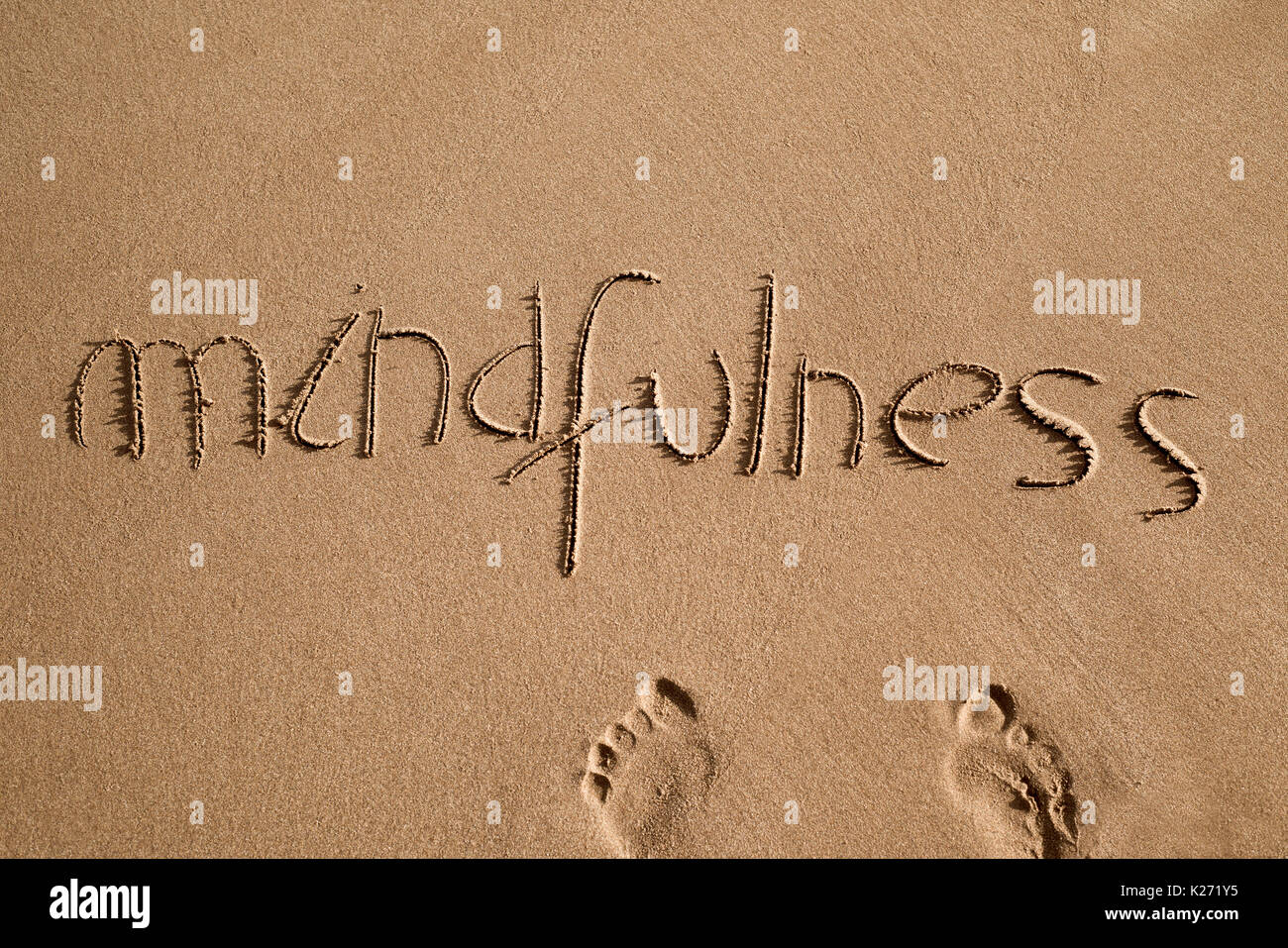 high-angle shot of the word mindfulness written in the sand of a beach and a pair of human footprints - Stock Image