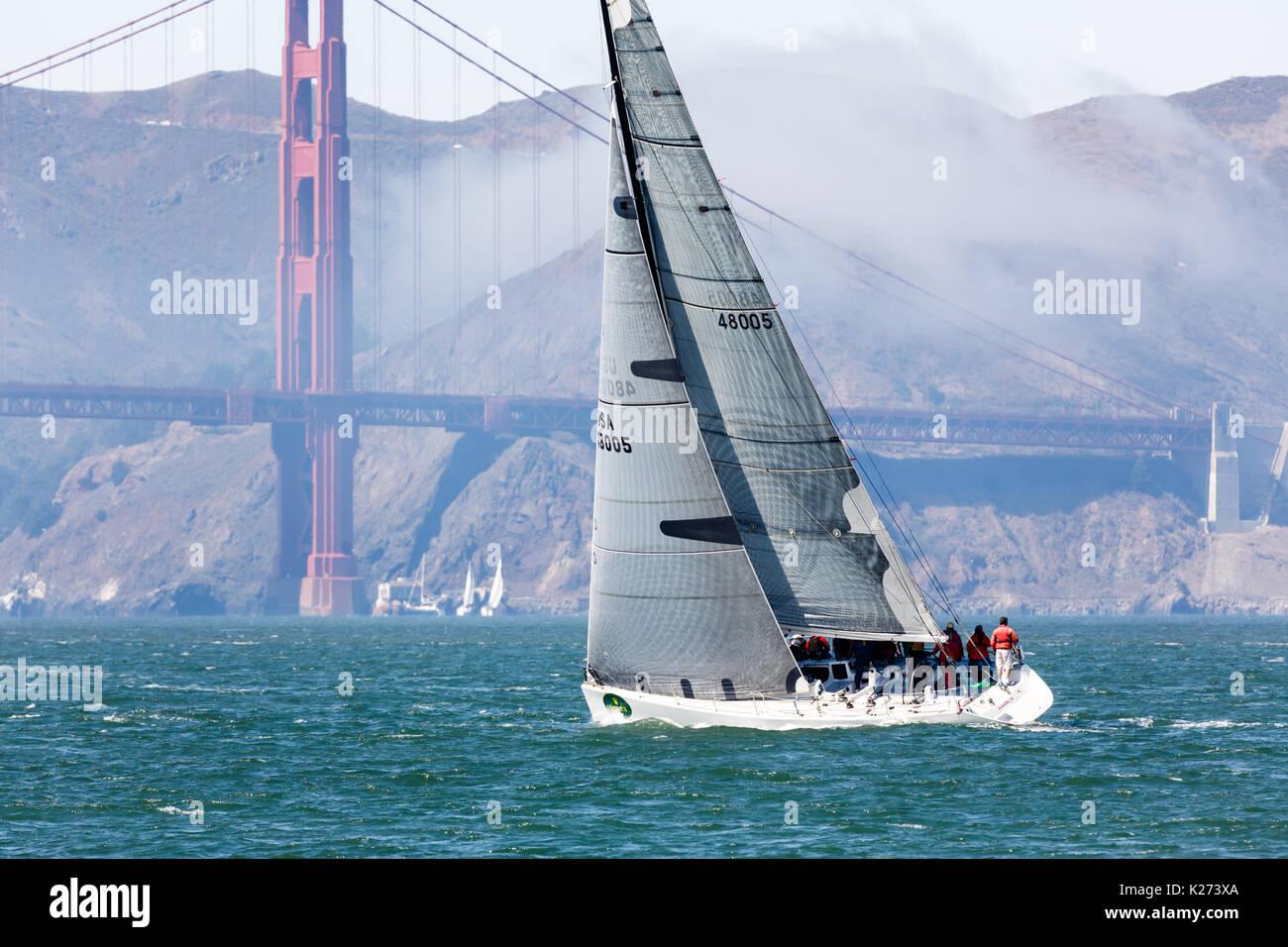Sailing swiftly toward the Ocean under the Golden Gate Bridge - Stock Image
