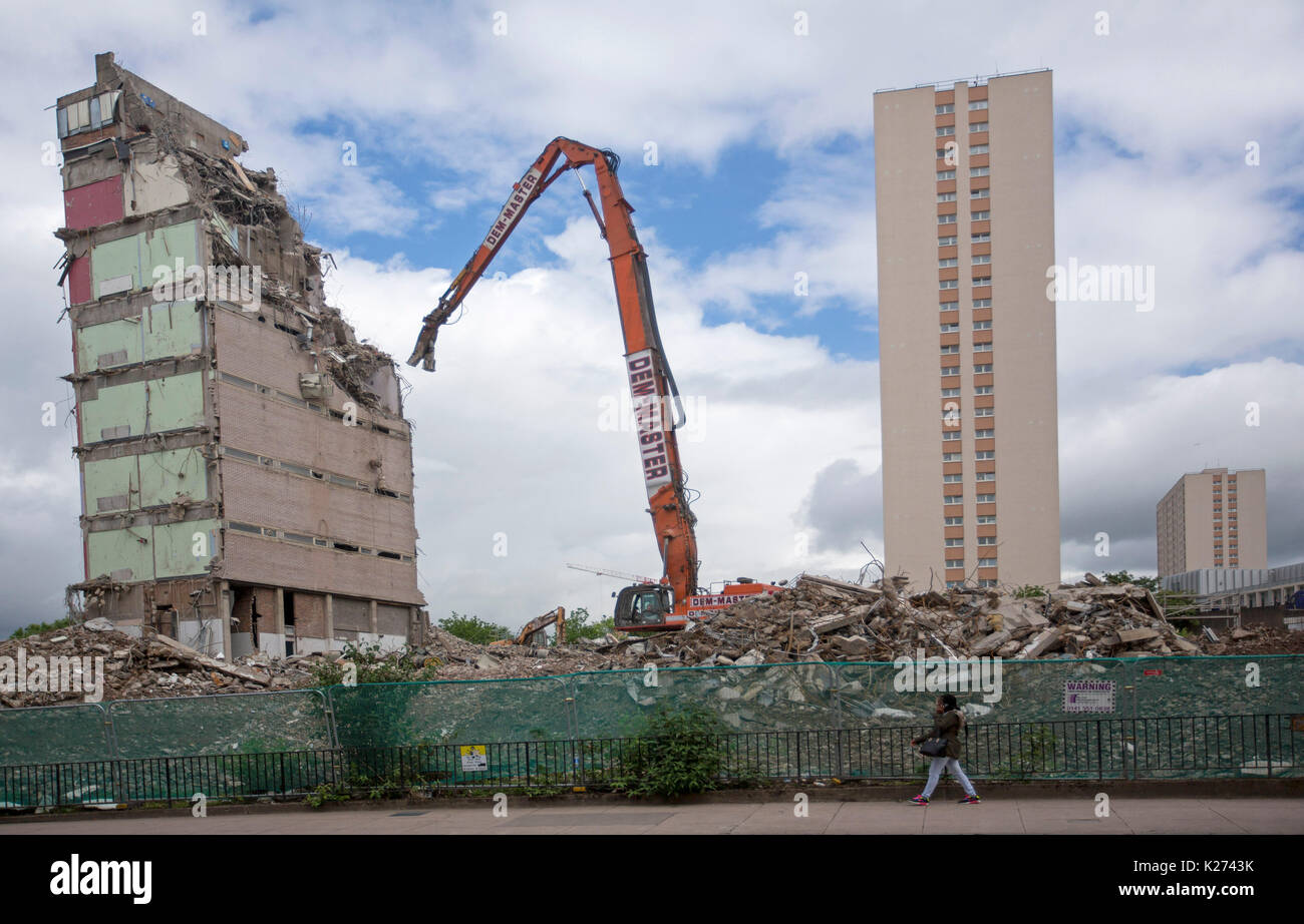 High rise apartment block being demolished by machine beside new building rising from rubble in city of Glasgow, Scotland - Stock Image