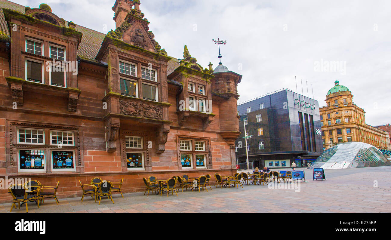 Ornate historic building, now a cafe, formerly entrance to St Enoch subway in Glasgow, with modern glass entrance to underground railway in background - Stock Image