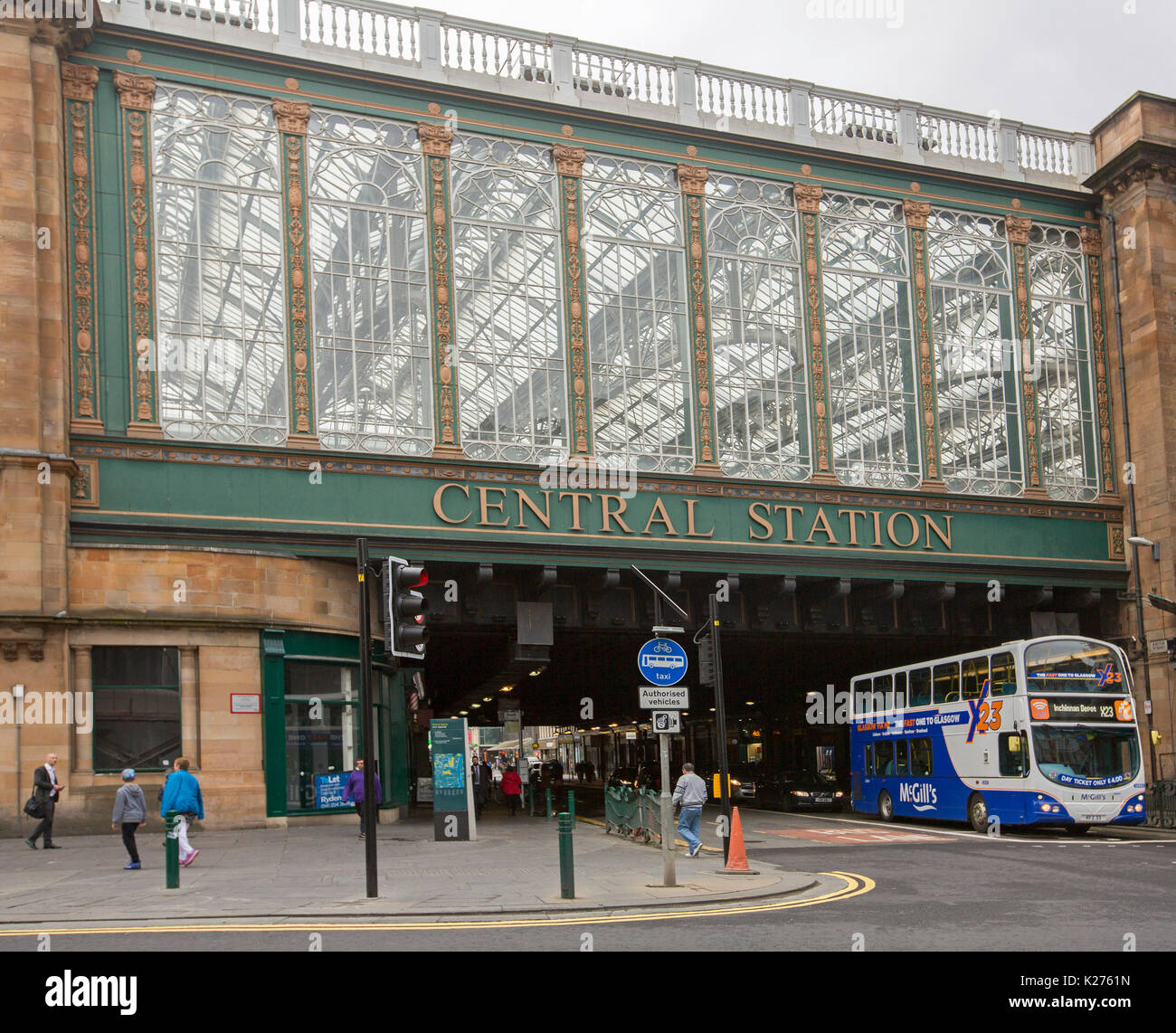Historic central railway station entrance with double decker bus emerging from tunnel  beneath high glass façade and roof in city of Glasgow, Scotland - Stock Image